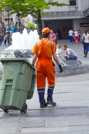 recolector de basura: Belgrade, Serbia - April 18, 2016: Anonymous municial worker with orange uniform collecting and emptying the trash containers in Republic Square, Belgrade on April 18, 2016 Editorial