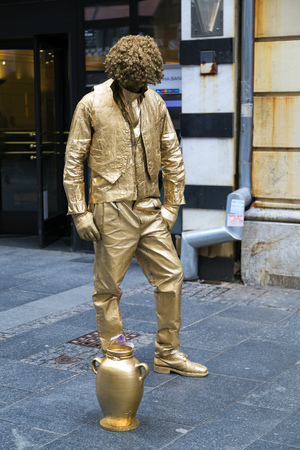 live work city: Belgrade, Serbia - April 18, 2016: Young entertainer, mime artist acting like a a bronze statue to earn money in Belgrade, Serbia on April 18, 2016. Editorial