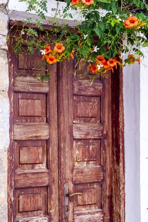ventanas abiertas: flores de color naranja contra la puerta de madera vieja