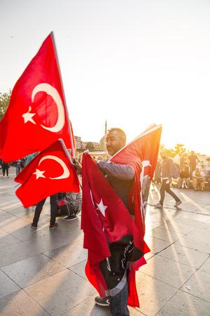 street vendor: ISTANBUL, TURKEY - May 7, 2016: Unidentified street vendor selling Turkish flags in Eminonu Square, Istanbul, Turkey.