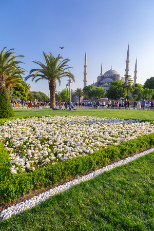 discovering: View of Sultanahmet square and the Blue Mosque with people walking, discovering and sitting around the historical area of Istanbul.