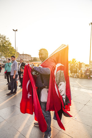 turkish people: ISTANBUL, TURKEY - May 7, 2016: Unidentified street vendor selling Turkish flags in Eminonu Square, Istanbul, Turkey.