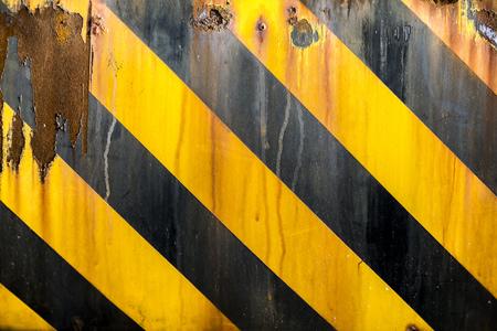 amarillo y negro: tiras de precaución amarillo y negro línea de pintado en superficie de metal, grunge fondo oxidado Foto de archivo
