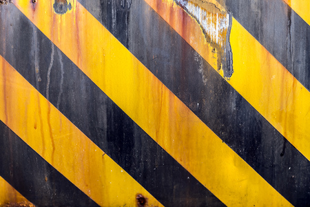 hazard: Black and yellow caution strips line painted on metal surface, rusty grunge background
