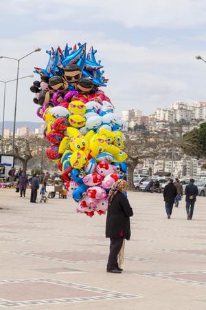 sidewalk sale: BURSA - MARCH 10, 2014 : Portrait of a decent Turkish lady selling balloons for kids  in the street on March 10, Gemlik, Bursa, Turkey