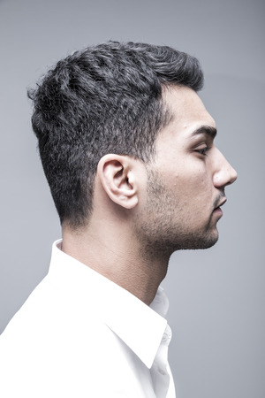 Young and attractive man in white shirt on grey background, studio side view portrait