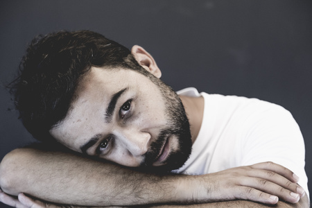 若い、スタジオ ポートレート、灰色の背景に魅力的な男性