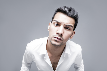 Young man in white shirt studio portrait, angry and confused facial expression