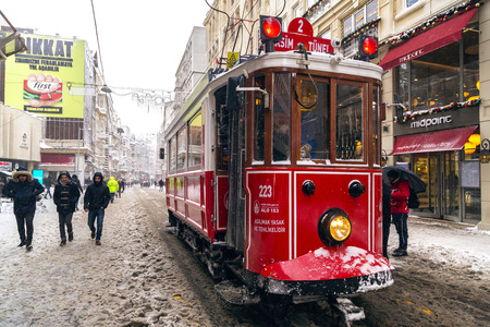 tramway: Istanbul, Turkey - January 7, 2017: Istanbul under heavy snow on January 7. The locals and visitors enjoy walking on snow on Istiklal Avenue and Taksim Square, Istanbul Turkey.