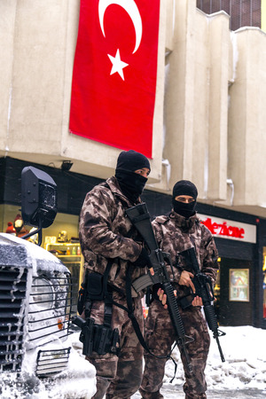 road safety: Istanbul, Turkey - January 8, 2017: Turkish Rapid Response Force Specialized Team (Cevik Kuvvet) geared with FN303 weapons and Scorpion APC (Akrep) guarding at the Istiklal Avenue on a snowy day. Editorial