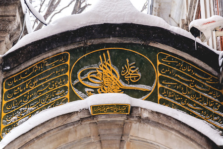Detail from the entrance of Galata Mawlawi House Museum (Galata Mevlevihanesi Muzesi) with Islamic calligraphy on a snowy day.