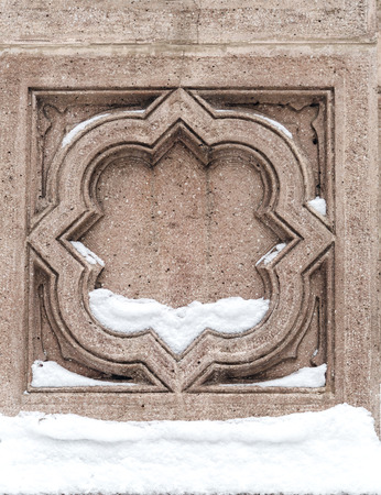 Ornamental detail on a stone wall partly covered with snow, architectural detail, winter concept