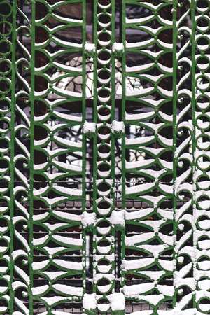 Wrought iron window fence covered with snow, close up pattern