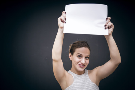 offset view: Young woman holding white empty paper, copy space for your text Stock Photo