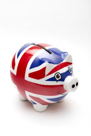 uk money: Porcelain piggy bank with UK flag print isolated on white
