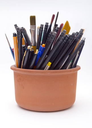Plenty of pens, pencils and brushes in an earthenware container