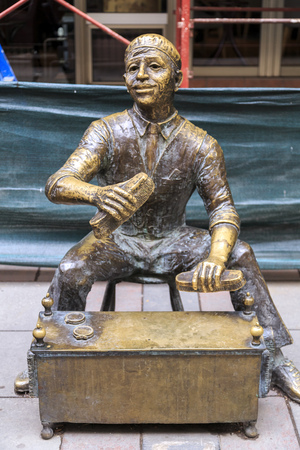 Skopje, Macedonia - April 9, 2017: Bronze sculpture of a shoeblack man at Makedonija Street in Skopje, Macedonia