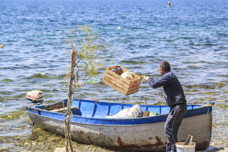 transfering: Ohrid, Macedonia - April 8, 2017: Municipality workers at work, collecting and transfering the garbage by a boat, Lake Ohrid, Macedonia. Editorial