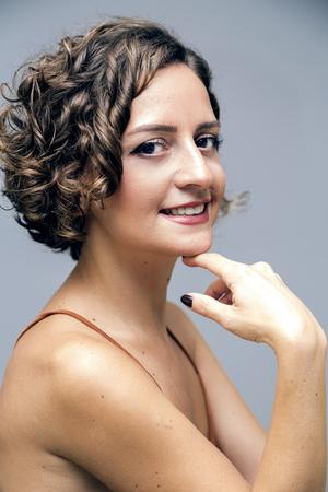 Beautiful female model wearing an orange silk bustier portrait shot on grey background