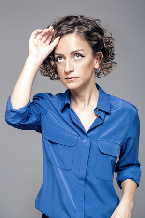 Young woman with short curly hair in blue blouse studio portrait Stock Photo