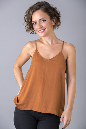 Beautiful female model wearing an orange silk bustier portrait shot on grey background