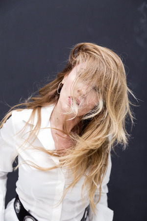 forties: Beautifully aging blonde lady in white shirt, studio portrait Stock Photo