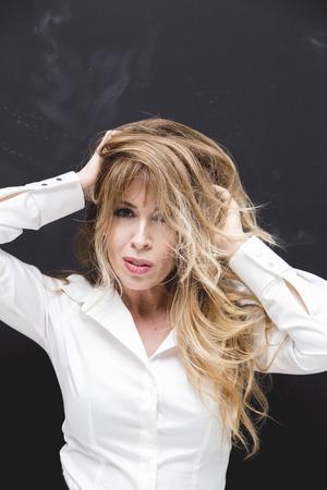 Beautifully aging blonde lady in white shirt, studio portrait Stock Photo