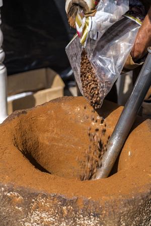 Turkse dibek-koffie vermaalt in een grote stenen vijzel met de traditionele handklopmethode