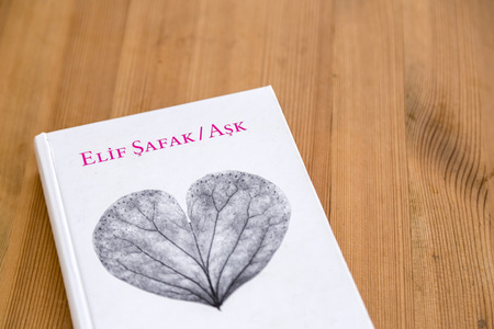 Istanbul, Turkey - October 12, 2017: Famous Turkish female author Elif Safaks best selling book Ask (Love) on wooden table. Published in 2009.
