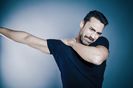 Young handsome man with beard and mustache having shoulder problems studio shot against blue background