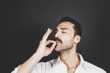 Young handsome man with beard and mustache kissing fingers, hand gesture for perfection Foto de archivo