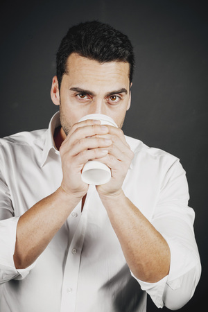 Young handsome man with beard and mustache drinking coffee, studio portrait Stock Photo