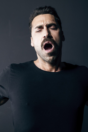 Young adult man with beard and moustache wearing a black t-shirt, feeling sleepy, studio portrait against black background Banco de Imagens