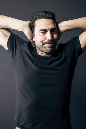 Young adult man with beard and moustache wearing a black t-shirt, feeling sleepy, studio portrait against black background Imagens