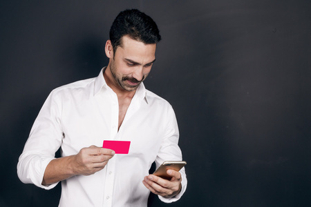 Young man with beard and mustache holding a mobile phone and credit card, online shopping and payment, studio shot, clipping paths for credit card included Stock Photo