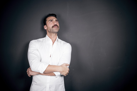 Young handsome man with beard and mustache wearing a white shirt posing against black background, studio portrait