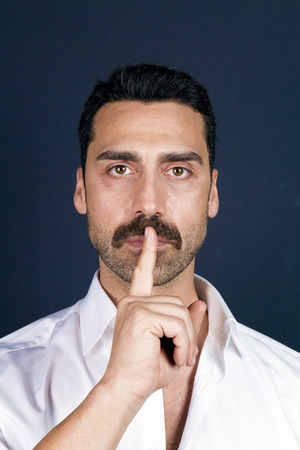 Young handsome man with beard and mustache showing hush sign, silence concept, studio portrait Stock Photo