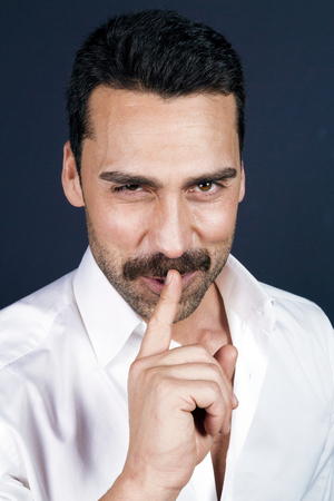 Young handsome man with beard and mustache showing hush sign, silence concept, studio portrait Foto de archivo