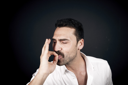 Young handsome man with beard and mustache kissing fingers, hand gesture for perfection Stock Photo
