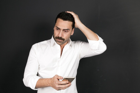 Young handsome man with beard and mustache using a mobile phone with a negative attitude, studio portrait Stock Photo