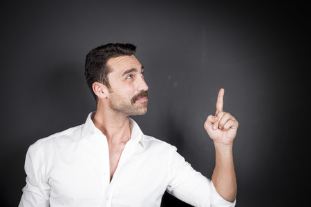 Young handsome man with beard and mustache showing direction for copy space, studio portrait Stock Photo