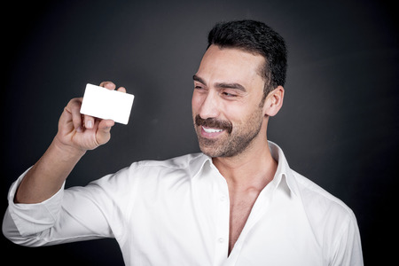 Young man with beard and mustache holding a business card or credit card, clipping paths for the card included