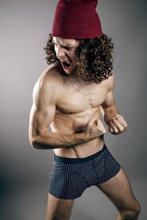 Attractive young man with long ginger curly hair posing with athletic topless body, studio portrait