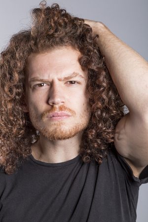 Attractive young man with long ginger curly hair studio portrait Stock Photo - 97040889