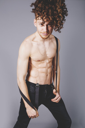 Attractive young man with long ginger curly hair and ripped muscled body wearing black jeans and belt suspendes, studio portrait Stock Photo