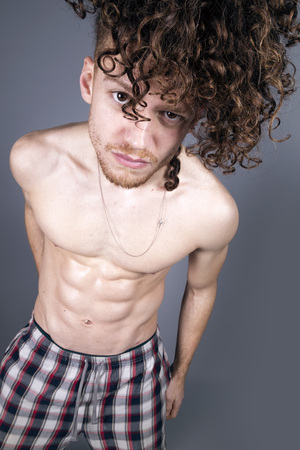Attractive young man with long ginger curly hair posing with athletic body in pajamas, studio portrait