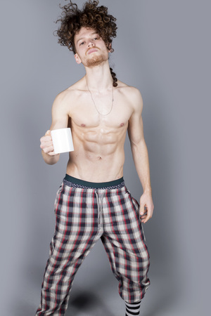 Attractive young man with long ginger curly hair having a cup of coffee or tea, studio portrait
