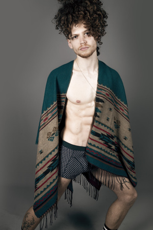 Attractive young man with long ginger curly hair posing with athletic body in a pancho, studio portrait