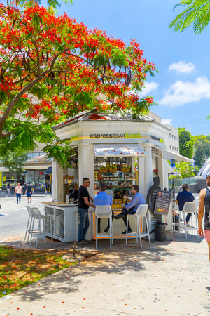 Tel Aviv, Israel - June 6, 2018: Buildings and people walking around at the famous Rothschild Boulevard in Tel Aviv, Israel. In the middle is the first kiosk built at the boulevard. Stockfoto - 104327809