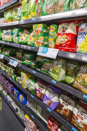 Tel Aviv, Israel - June 6, 2018: Various products sold at a grocery store in Tel Aviv, Israel. Snacks, crakers and cookies on the shelves.